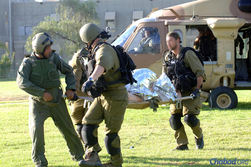 A wounded Israeli soldier is carried into Soroka hospital in the southern city of Beersheva. (Photo: Flash90)