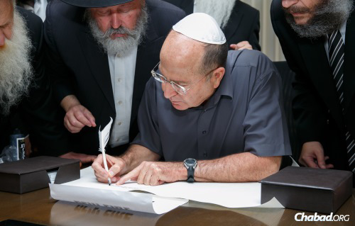Defense Minister Moshe Ya'alon pens the first letter of a Torah scroll written for the security of the troops. To his left is the sofer, Rabbi Mordechai Lishner; on his right is Rabbi Yosef Yitzchak Aharonov, director of the Chabad Youth Organization in Israel. (Photo: Shalom Lavi)