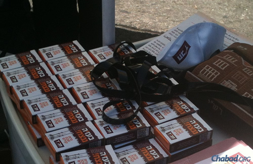 """Hundreds of brochures a day with the """"With G-d's help, we will prevail"""" theme are handed out daily in Jerusalem's Machane Yehuda open-air market."""