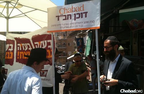 Rabbi Tzvi Ruderman, right, with rabbinical students in Jerusalem's Machane Yehuda market, as a visitor to Jerusalem wraps tefillin.