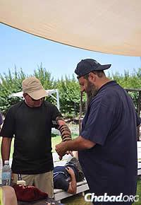 Andrusier wraps tefillin with participant Steven Sztab