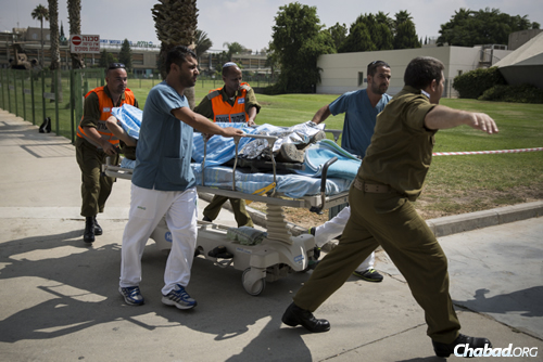 An IDF soldier wounded in combat in Gaza is led to the emergency room at Soroka hospital in Beersheva, after being evacuated from the field by helicopter. (Photo: Hadas Parush/Flash90)