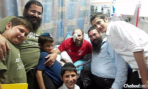 A contingent of Chabad representatives—from left, Yossi Cohen, 12; Rabbi Itzhak Naimark, Chabad of Hebron; Yisrael Cohen, 8; Shay Cohen, 14; Rabbi Danny Cohen, co-director of Chabad of Hebron; and Menny Cohen, 17—visit Dvir, an injured Israeli Defense Forces soldier who must undergo multiple surgeries to save his right eye.