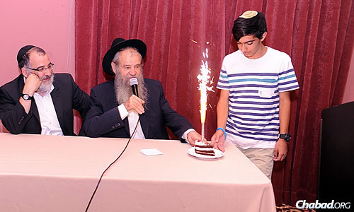 Rabbi Amrom Blau, director of Colel Chabad, announces a boy's birthday, complete with a slice of cake. Seated to his left is Rabbi Mendi Blau, director of Colel Chabad in Israel.