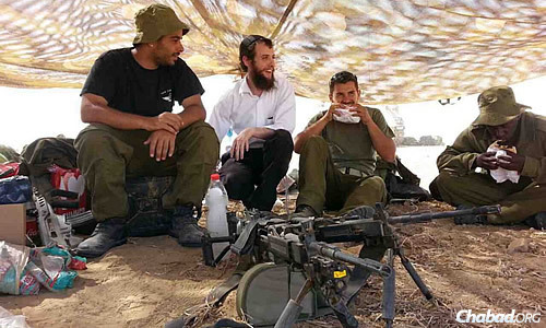 A donor surprised the soldiers on Sunday by having Chabad deliver 350 hot shwarmas in pita to the field. Rabbi Refael Brod, co-director of Chabad of Kiryat Arba in Hebron, talks with the men as they enjoy their meal.