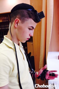 The camp offers refugees opportunities to participate in Jewish life, like this teen donning tefillin and praying.
