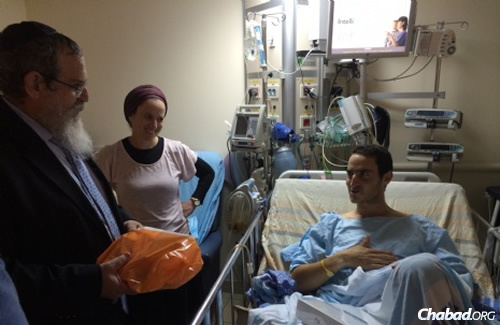 Rabbi Dovid Eliezrie hands a new iPad to a wounded Israeli soldier.