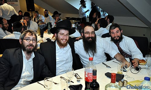 Enjoying a meal and some down time are, from left, Rabbi Mendy Lent, Rabbi Shneur Cohen, Rabbi Eli Pink and Rabbi Odom Brandman.