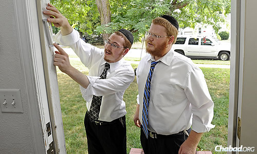 """""""Roving Rabbis"""" Yosef Sharfstein, left, and Shmuel Lefkowitz, both 24 and from New York, are headed to South Dakota as they did last August, seen here hanging a mezuzah on a Jewish home. (Photo: Emily Spartz/Sioux Falls Argus Leader)"""