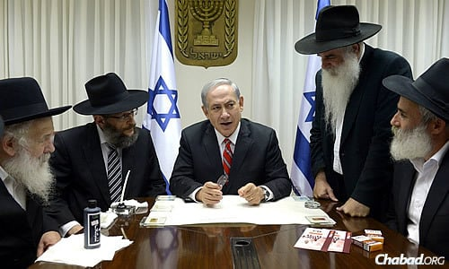 Israeli Prime Minister Benjamin Netanyahu, at a ceremony with Chabad rabbis and representatives, prepares to pen a letter in a Sefer Torah honoring soldiers of the Israel Defense Forces.