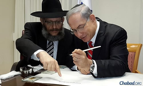 Aharonov points to a specific part of the text as the prime minister finishes the inscribing.