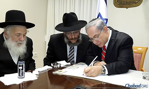 Israel's Prime Minister Benjamin Netanyahu pens a letter for a new Torah Scroll sponsored by the Chabad Youth Organization in Israel on behalf of the safety of everyone in the Holy Land.
