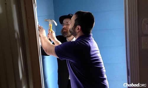 Rabbi Chaim Lazaroff of Houston, in the background, helps Brian Levinson affix his new mezuzah. (Photo Jillian Levinson)