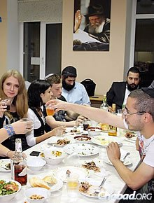 """""""The Stars"""" college-age student group takes time to enjoy a meal together."""