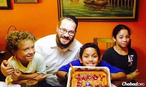 Rabbi Yaakov Raskin celebrates a birthday with Jewish children who attended a newly formed day camp in Jamaica this summer.