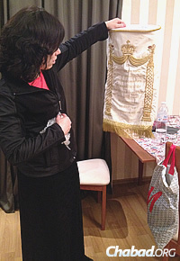 Dina Vishedski, co-director of Chabad-Lubavitch of Donetsk now settled in Kiev, holds a Torah-scroll cover from her home town. (Photo: Dovid Margolin)