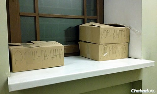 """These boxes read """"Rosh Hashanah"""" and """"Yom Kippur,"""" and include items for the upcoming High Holidays. (Photo: Dovid Margolin)"""