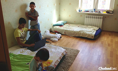 Two different families with children—a total of eight people—live in this two-room apartment with little furniture. Here, former Donetsk resident Marina's sons Anver, Rinat and Yosef try to occupy their time. (Photo: Dovid Margolin)
