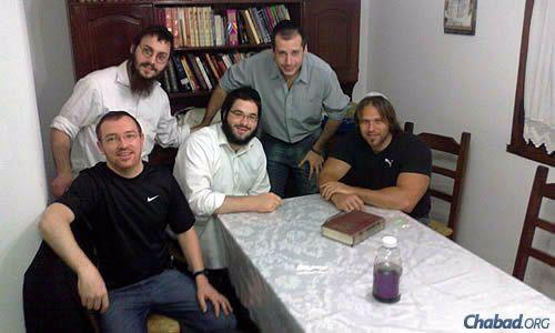 El hombre de camisa gris contactó a JNet pidiendo ayuda con un minián para las festividades y fue asistido por los estudiantes rabínicos Sholom Ver Levy, sentado, y Shloimi Setton (camisa blanca), quienes viajaron desde Buenos Aires. Los otros dos hombres participaron de los servicios de Shabat y Rosh Hashana, con un seguimiento planificado para Iom Kipur.