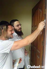 Setton ayuda a uno de los residentes a colocar una mezuzá en su hogar en la víspera de Iom Kipur