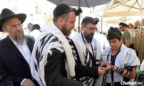Wrapping tefillin with the bar mitzvah boy, Roee Mendelovich, from left: Rabbi Aharon Prus of the Lubavitch Youth Organization of Israel; Rabbi Yossi Swerdlov, associate director of the Chabad Terror Victims Project; and Rabbi Menachem Kutner, director of the Chabad Terror Victims Project. (Photo: Meir Alfasi)