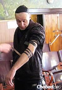 A prisoner named Kuperman is assisted in wrapping tefillin.