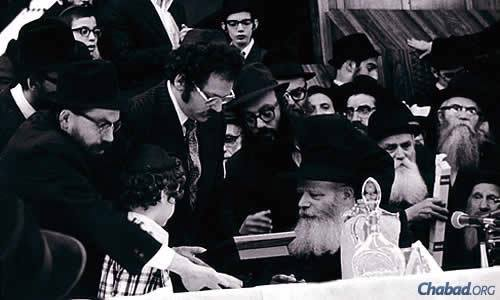 "Circa 1975: Stuart Nelkin and his son, Jay, join Rabbi Shimon Lazaroff, left, of Chabad Lubavitch Center Regional Headquarters in Houston in presenting the key of the Chabad House in Austin, Texas, to the Rebbe. Lazaroff's advice to young shluchim mirrors the Rebbe's words: ""Be totally dedicated ... and the children will look at you, and see what you do and how you behave, and this will rub off on them."" (Photo: Chabad of Texas Archives)"
