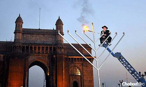 Rabbi Shimon Rosenberg of Afula, Israel, the father of Rivkah Holtzberg, lights a 25-foot steel menorah during Chanukah 2008 in front of the Gateway of India in Mumbai just weeks after his daughter and son-in-law, Rabbi Gavriel Holtzberg, were killed in a terrorist attack. Gavriel Holtzberg would light that menorah each year. (Photo by Serge Attal/Flash90)