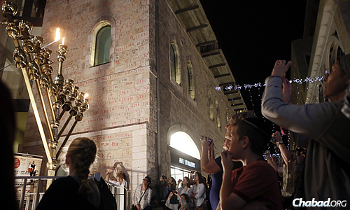 Onlookers view the lighting of the first candle on a menorah at the Mamilla Mall in Jerusalem, outside the Old City's Jaffa Gate. Even in Israel, Chabad has heightened awareness of Chanukah for millions of residents and tourists from around the world. (Photo: Miriam Alster/Flash90)