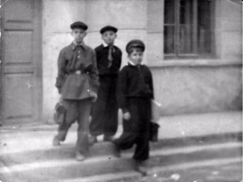 ילדים יהודיים יוצאים מבית הספר העממי בסמרקנד. הנער האמצעי עונד את העניבה האדומה של הפיונרים.