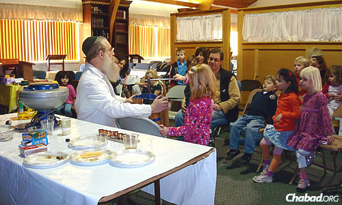 """Rabbi Yisroel Engel, co-director of Chabad-Lubavitch of Colorado, has been holding """"Chanukah Factory"""" workshops for children for almost 30 years, showing them how to press oil from olives for use in the menorah."""