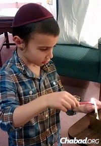 The 5-year-old helps one resident with the Chanukah lights.
