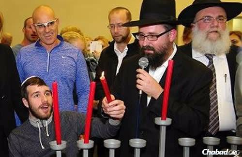 """It was a Chanukah to remember for recovering Sgt. Ohad Benyishai, shown here holding the """"shamash"""" (helper candle) to light the menorah."""
