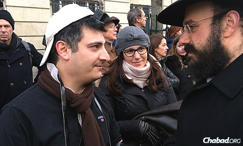 In the midst of more than 1.5 million people at the rally on Sunday, Chabad-Lubavitch emissaries, students and volunteers were out in full force. Here, Rabbi Yosef Yitzchok Amar wraps tefillin and talks with a man in the crowd.