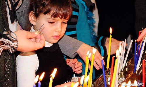 A child takes care to kindle the Chanukah candles.