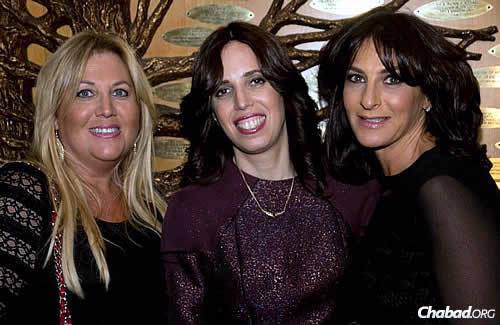 Chanie Kramer, co-director of the Chabad Center for Jewish Life in Merrick, center, is flanked by two local residents and organizers of the group, Cindy Knoll, left, and Lisa Fessler.