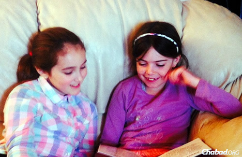 One of the Namdar girls, left, studies with a friend. The children are social through their online school and with all of the activities at the Chabad House.