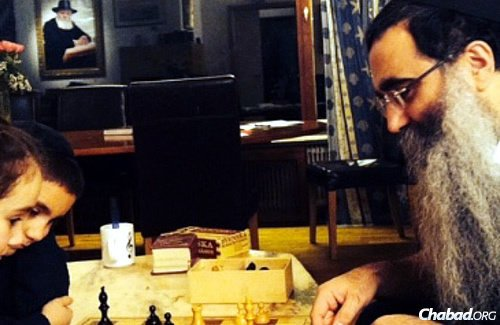 The rabbi plays a little chess with the younger children after a day of study and as part of family time.