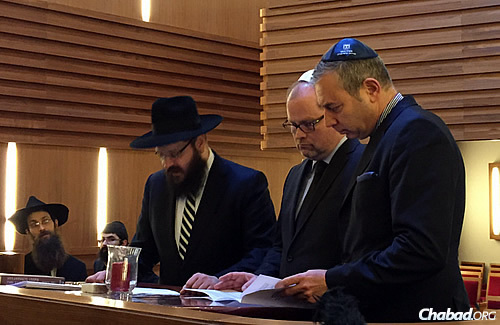 Rabbi Yehuda Teichtal, rabbi of the Berlin's Jewish community, left, and attorney Nathan Gelbart, chairman of Keren Hayesod Germany and a member of the Central Council of Jews in Germany's arbitration court, right, pray at the Rohr Chabad Center in Berlin with visitor Christian Lange, Parliamentary State Secretary at the Federal Ministry of Justice and Consumer Protection in Berlin, Germany. (Photo: Federal Ministry of Justice)