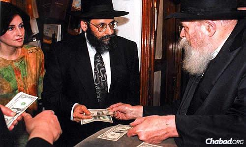 The Lipskars receive a dollar from the Rebbe—Rabbi Menachem M. Schneerson, of righteous memory—in the Crown Heights neighborhood of Brooklyn, N.Y. The Rebbe had earlier given them a blessing to move to the village of Bal Harbour, which was once restricted to Jews.