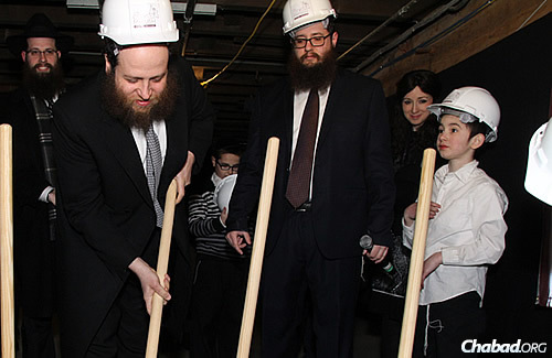 Rabbi Baruch Hertz, left, director of Chabad of Lakeview and Congregation B'nei Ruven in Chicago, takes a stab at some dirt at a Feb. 20 event across from the old mikvah site and celebrating the groundbreaking of a new one.
