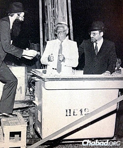 Rabbi Tzvi Grunblatt, director of Chabad of Argentina, hands materials to David Goldberg, president of the Jewish umbrella organization DAIA, to light the Chanukah candles on the first public menorah in Buenos Aires in 1985. At right is Israeli ambassador to Argentina Dr. Efraim Tari.