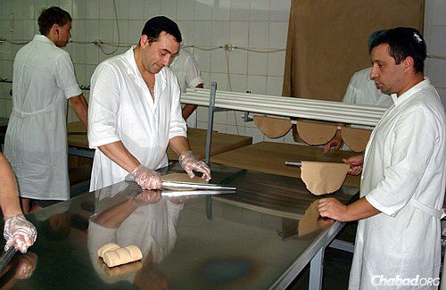 Workers at the Dnepropetrovsk matzah bakery rolling out traditional round matzahs. The Tiferes Hamatzos bakery employs 100 workers, among them exiles from the war-torn eastern regions of Donetsk and Lugansk.