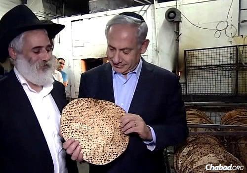 Mayor of Kfar Chabad Benyamin Lipshitz watches as Israeli Prime Minister Benjamin Netanyahu admires a matzah he helped bake.