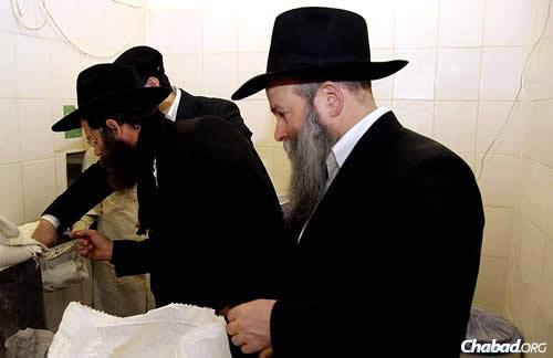 Ashkenazi inspects the flour, as Kaminezki looks on. (Photo: DJC.com.ua)
