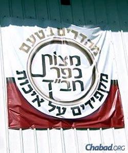 """""""Matzot Kfar Chabad."""" The bakery sign reads: """"Amazing taste, exacting quality."""""""
