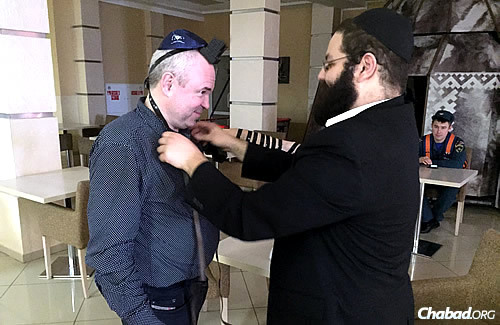 The rabbi helps Russian Deaf historian Victor Palenny put on tefillin.