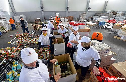 Voluntários empacotam caixas de itens casher para Pessach, como parte da maior remessa feita de alimentos do Colel Chabad até hoje, para serem distribuídos aos necessitados antes da festa. (Foto: Israel Bardugo)