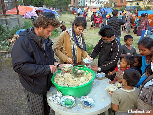 """Serving a hot dish of """"dal bhat,"""" a lentils-and-rice local stapled, and pita bread in Nepal. (Photo: David Karsenty/Chabad of Nepal)"""