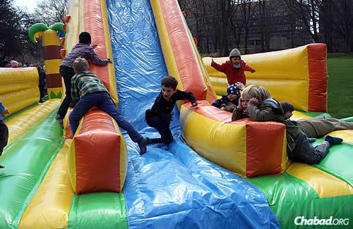 Children scramble on a moon bounce in Fælledparken during a previous Lag BaOmer event.